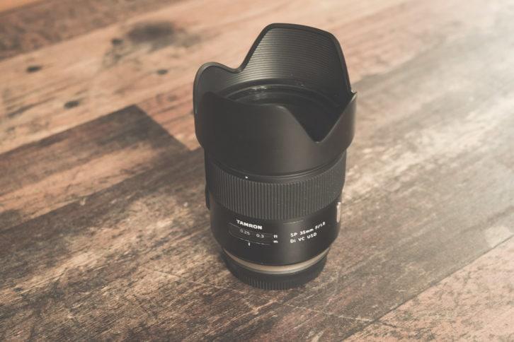 Das getestete Tamron 35mm f/1,8 VC USD mit Gegenlichtblende aufrecht stehend